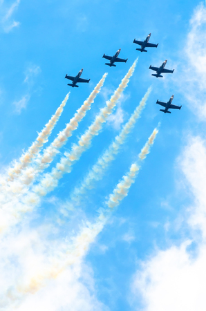 Group of fighter planes fly up with a smoke track against a blue sky with clouds Stock Photo