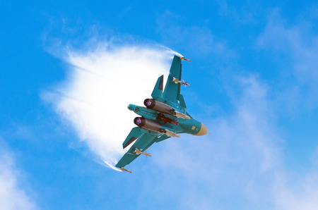 Battle fighter jet aircraft flying dives breaking clouds on a blue sky
