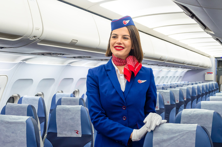Charming Stewardess Dressed In Uniform in the passenger cabin of the aircraft. Russia, Saint-Petersburg. 23 November, 2017