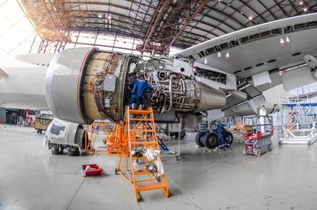 Specialistische monteur repareert het onderhoud van een grote motor van een passagiersvliegtuig in een hangar