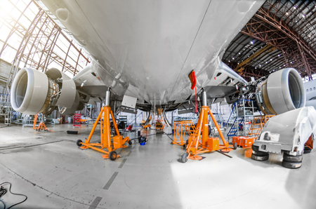 A large aircraft for service maintenance on special jacks in the hangar