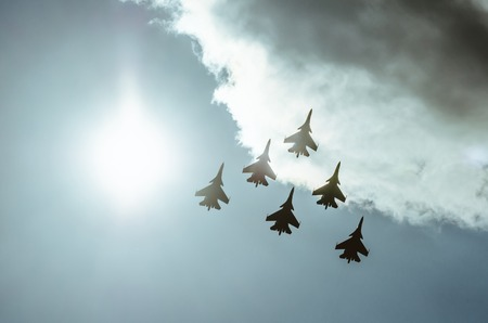 Group of fighters in the sky in the violet sunshine lighted up