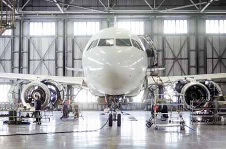 Passenger aircraft on maintenance of engine and fuselage repair in airport hangar