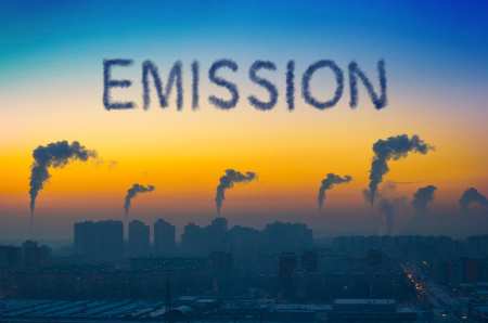 Evening view of the industrial landscape of the city with smoke emissions from chimneys at sunset