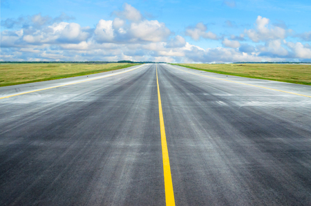Asphalt road runway with a dividing strip in the horizon