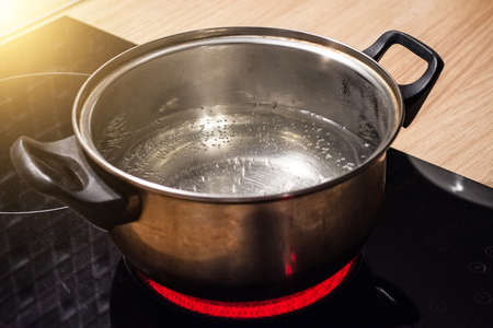 Metal pan with boiling water on the induction cooker red hot plate 免版税图像