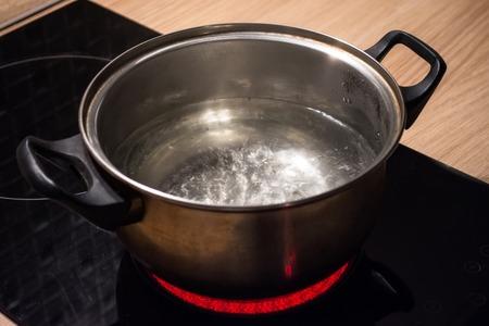 誘導炊飯器赤いホットプレートに沸騰したお湯を入れた金属鍋 写真素材