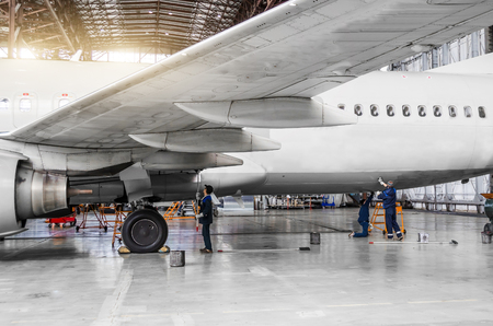 Several people wash the aircraft in the hangar for maintenance, view of the chassis, wing and tail Archivio Fotografico