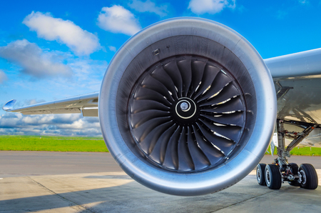 Engine of the modern aircraft close up and the blue clouds in the sky Stock Photo