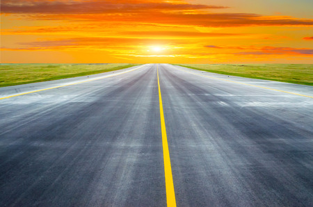 Runway and road goes into the horizon at sunset dawn