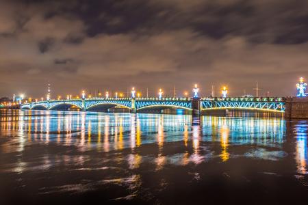The Trinity Bridge night with backlight illumination lights with reflection in the river Neva, Saint-Petersburg