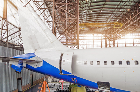 Passenger aircraft on maintenance, a view of the tail and the rear of the fuselage in airport hangar Stock Photo
