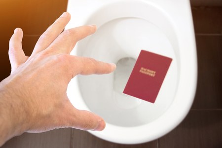 Hand holds the citizens passport over the toilet, throw out his passport. Concept - change of citizenship, loss of passport, political problems, infringement of rights
