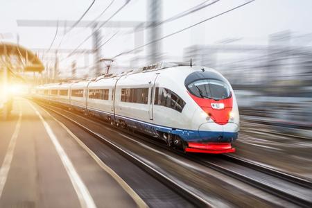 Szybki pociąg jedzie z dużą prędkością na dworcu kolejowym w mieście