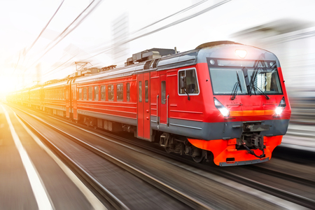 Red passenger train with headlights on rushing through the railway in the evening Фото со стока