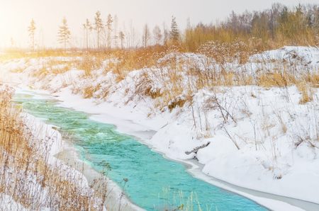 Rough river at the foot of the mountains in a turquoise, blue, green forest in winter, ice and snow around the landscape