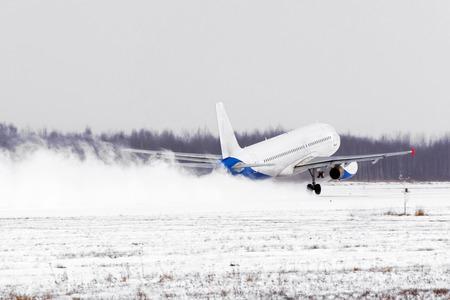 吹雪、冬の強風の悪天候で雪に覆われた滑走路空港から離陸する飛行機