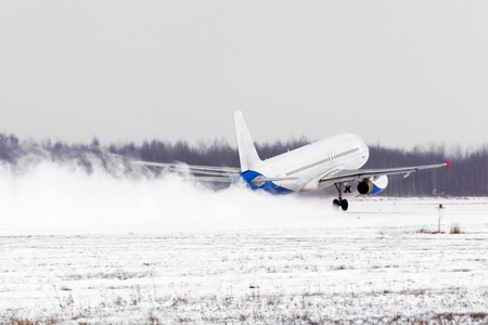 Airplane take off from the snow-covered runway airport in bad weather during a snow storm, a strong wind in the winter