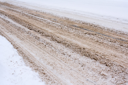 Snow-covered road mixed with mud, salt, chemical reagents and, traces of cars