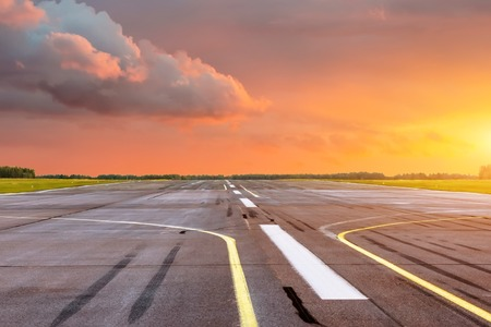 Runway at the airport the horizon at sunset in the center of the sun Фото со стока