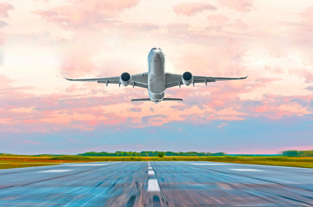 Passenger airplane landing at sunset on a runway Stock Photo