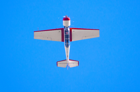 Airplane flys upside down in the blue sky