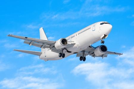 Passagiersvliegtuig met het chassis vrijgegeven vóór de landing op de luchthaven tegen de blauwe hemel