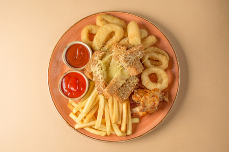 French fries, onion rings, chicken wings, rusks, a snack to beer on a large plate with two sauces on a brown background. Top view Stock Photo
