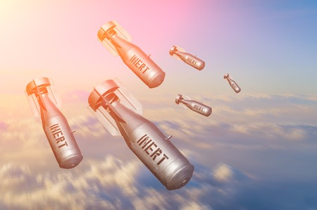 Falling bombs weapons charges dropped from a fighter combat aircraft high in the sky, a view of clouds and land Stock Photo