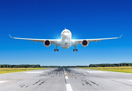 Passenger airplane with bright landing lights landing at in good clear weather with a blue sky on a runway