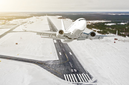 Airplane is climb flight level high view in the air, against the background of the winter airport of the runway, city, snow, forests and roads