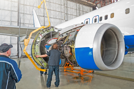 Assembling, replacing engine parts of the aircraft after repair. Specialist mechanic controls the crane when assembling an engine on the wing of an airplane. Concept maintenance of aircraft