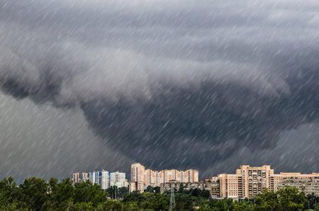 Tornado, funnel clouds during a thunderstorm a heavy rain downpour over the city 免版税图像