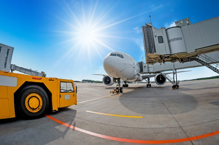 Parking at the airport, airplane at the teletrap. Aerodrome tractor is ready for towing and departure of the aircraft. Against the background of a blue sky and bright sun, nice weather