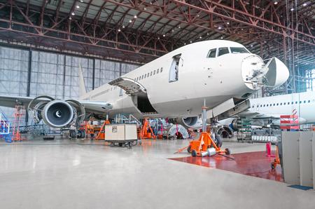Avión de pasajeros en mantenimiento de motor y reparación de fuselaje en hangar del aeropuerto. Aeronaves con capó abierto en la nariz y motores, así como el maletero Foto de archivo