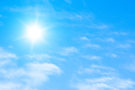 The sun with bright rays in the blue sky with white light clouds Stock Photo