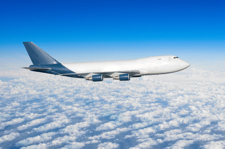Airplane with four engines, truck without portholes in the sky above the clouds flight journey sun height Stock Photo