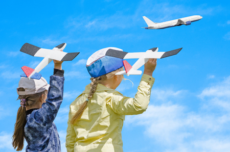Two girls kid playing with toy airplane and a real passenger plane taking off in the sky, against blue summer sky background. Concept - inoculating the love of children for aviation