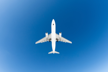 Passenger airplane. View exactly from below, white silhouette against the blue sky
