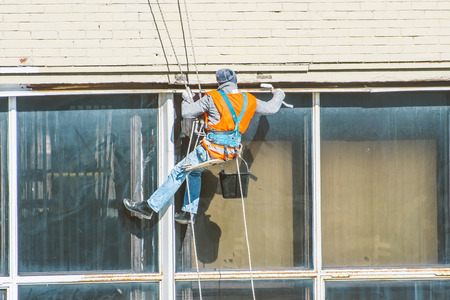 Industrial mountaineering, a man restores joints in windows and washes them Banco de Imagens