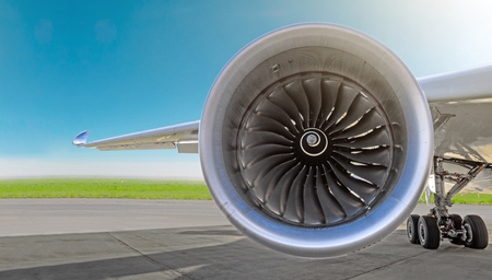 Aircraft jet engine close-up, airplane wing and chassis of landing gear wheel parked at the airport on a sky background, panorama