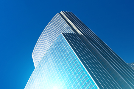 Building of a glass skyscraper with a blue flare against the sun against a blue sky