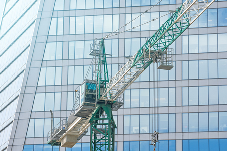 Construction crane on building skyscraper apartment house, on a background of glass texture of financial offices windows