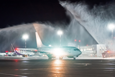 Meeting a new aircraft at a night airport, the tradition of wash spray pouring water from fire trucks