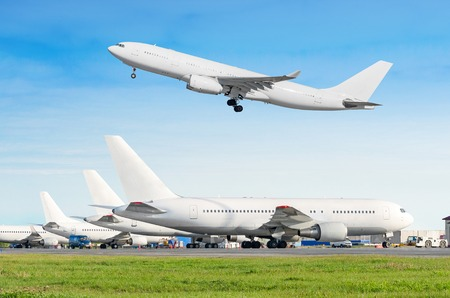 Passenger aircraft row, airplane parked on service before departure at the airport, other plane push back tow. One two-story airplane take off from the runway in the blue sky Stock Photo