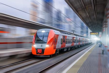 Hochgeschwindigkeitszug fährt mit hoher Geschwindigkeit am Bahnhof in der Stadt Standard-Bild - 101047872
