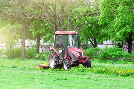 Red tractor and lawn mower, shears lawns in the alleys in the park