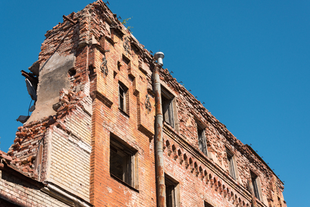 Old destroyed houses of brick with windows, wall