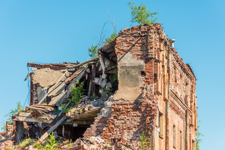 Old destroyed houses of brick with windows, overgrown with plants Stock Photo