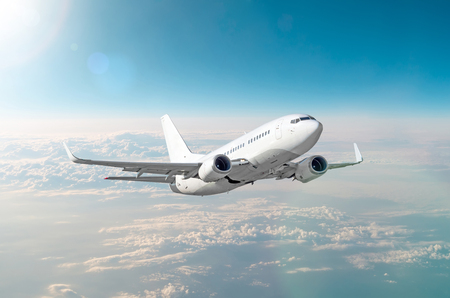 Passenger white airplane flies in a blue sky with a bright sun